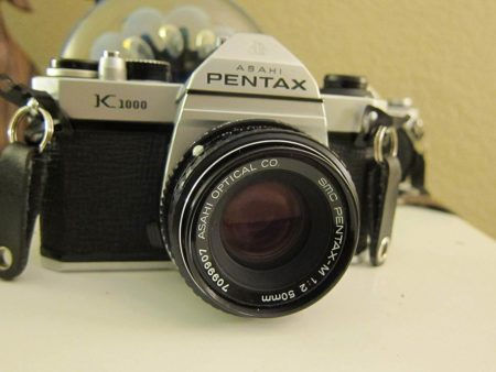 This is an image of Pentax K1000 Manual Focus SLR Film Camera with Pentax 50mm Lens