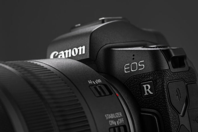 Image of Canon EOS R Mirrorless Digital Camera with Canon EF 24-105mm f4L IS USM lens on a black background. Canon is the world largest SLR camera manufacturer.