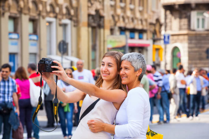 Mother and daughter taking selfie with entry level Nikon photo camera