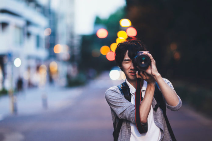 A young Japanese man is taking photos at night in Tokyo