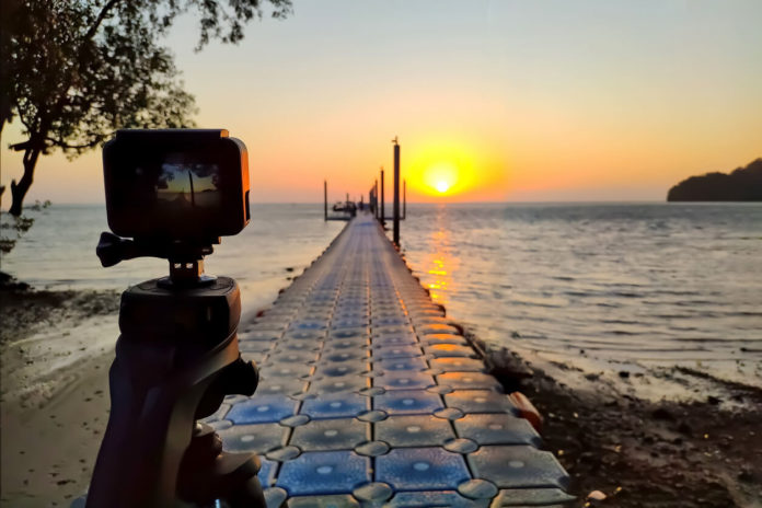 gopro alternative Action camera mounted on a tripod photograph the pier and sunrise on the beach