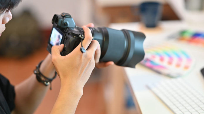 Close up Cameraman checking with professional camera Photography Photographer working in creative workplace.
