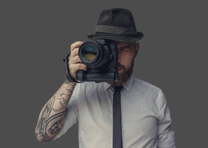 Digital photographer with an expensive digital camera in white shirt and casual hat. Isolated on grey background.