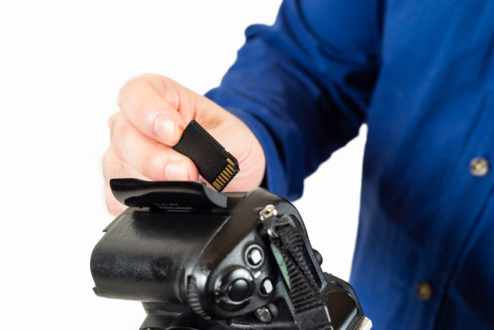 Image contains a man inserting a memory card into his camera.